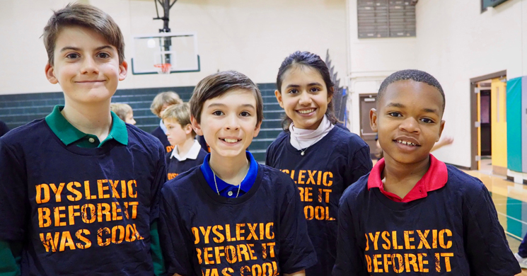 "Four children wearing shirts which state ""dyslexic before it was cool"""