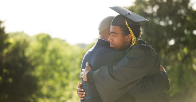 College graduate hugging his father