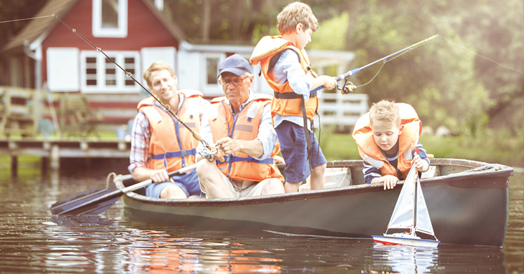 An image of a grandfather, father and two young sons fishing evokes legacy and estate planning.