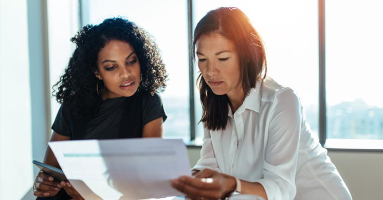An image of two women looking at a paper in a brightly lit office building represents understanding of what a credit score means.