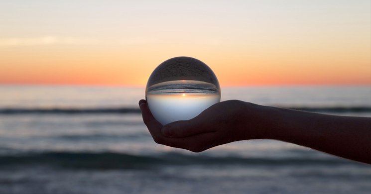 an image of the sunset shining through a crystal ball evokes questions about investing to further social and global causes