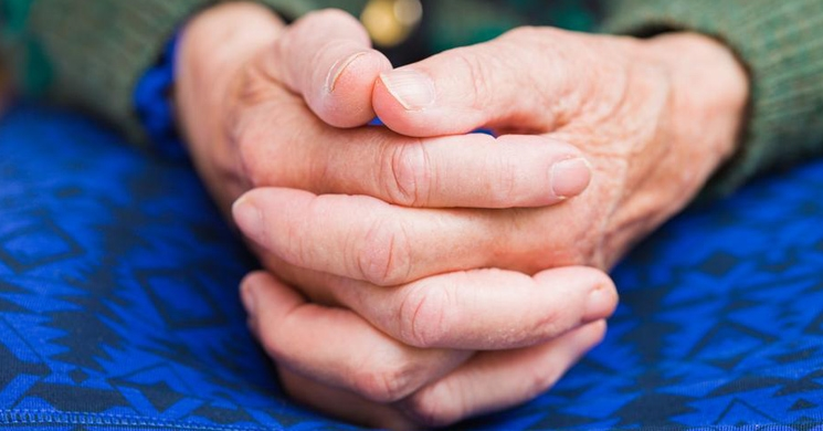an image of an elderly person's folded hands bring to mind the issues involved in long-term care