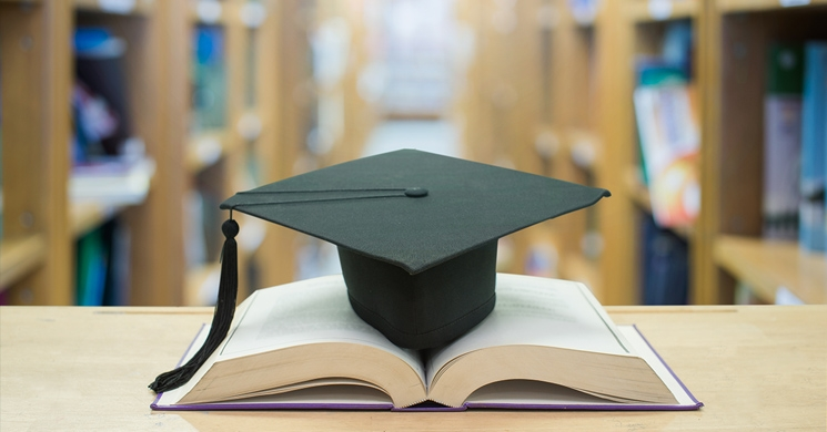 an image of a graduate's hat in a library brings to mind the question of what to gift to give a student who is graduating