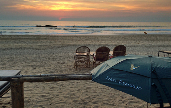 First Republic Bank umbrella on a beach in Agonda at sunset.