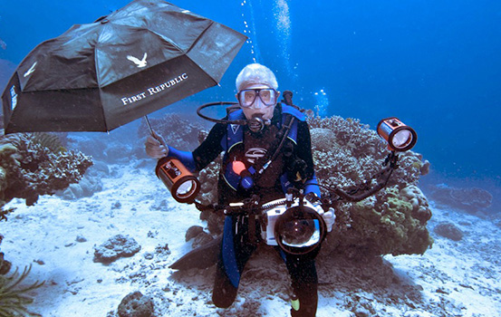 First Republic Bank client Ed Kelly SCUBA diving and holding a First Republic Bank umbrella under water.